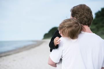 Vater trägt Kind auf dem Arm am Strand