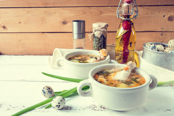 Cheese soup with chicken, herbs and vegetable. Cheese, cucumbers and herbs on wooden table. Light background.
