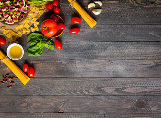 Pasta background. Several types of dry pasta with vegetables over a wooden table.