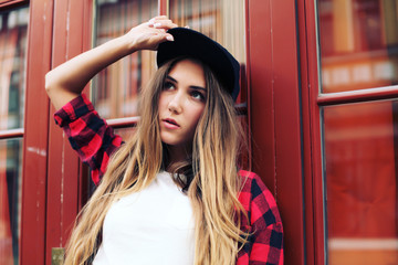 Close up portrait of pretty girl with amazing long ombre hairs, black sportive hat, casual trendy white shirt, and plaid red t-shirt.