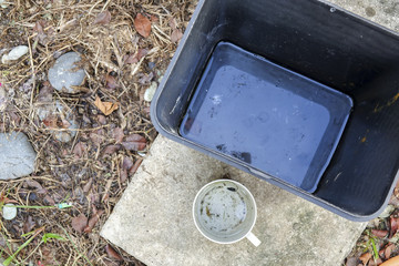 Stagnan water in rubbish container and plastic cup potentially for musquitoes breeding ground. Blurred image.