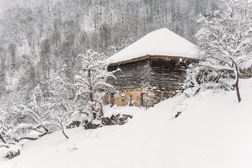 Wooden mountain cottage covered in snow