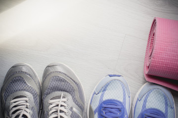 Dirty sport shoes on  floor with yoga mat at home. Lifestyle con