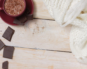 Milk chocolate in a cup on a saucer on a light wooden background