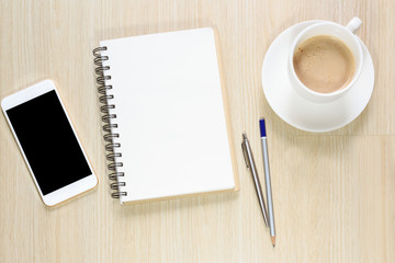 Top view of blank notepad on office desk with smartphone, pen and coffee