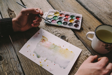 Men painting with a watercolor brush, white old metal cup, filled with dirty water, a piece of watercolor paper and used watercolors on rough wooden table.