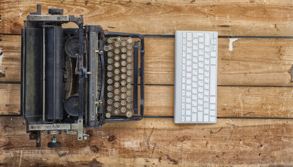 Old typewriter and a new keyboard on vintage wooden background photographed in daylight. New and old technology