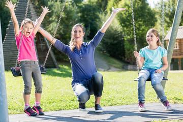 Familie mit Mutter und zwei Mädchen auf Spielplatz Schaukel