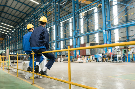 Rear view of two blue-collar workers during break