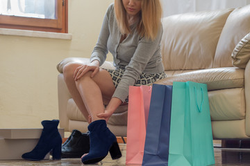 shopaholic woman trying new shoes sitting on sofa, shopping bags and footwear boxes on her side