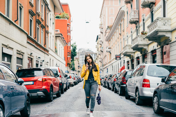 Young beautiful caucasian brown hair woman walking outdoor in the city talking smart phone - communication, talking, discussing concept
