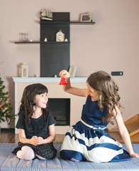 two  sisters amusing themselves with a bell