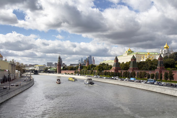 Tour boats / ships are on Moskva rive. Dramatic cloudy sky is in the view. Dormition Cathedral, Kremlin Palace and Borovitskaya Tower are on the right side of the image.
