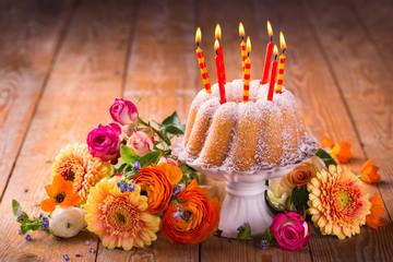 Geburtstagskuchen mit Kerzen und Blumen