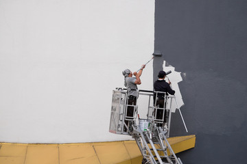 Two worker are paiting exterior of building