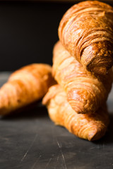 Stack of freshly baked croissants on black background, golden delicious crust,close up,food photography