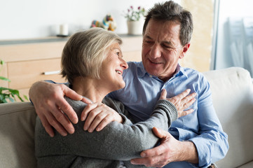 Senior couple sitting on a couch in living room, hugging