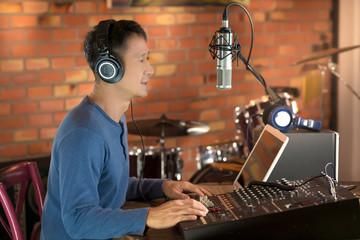 DJ working at radio broadcasting studio,hands adjusting volume and keyboard. Male radio broadcaster using laptop computer and audio mixer controlling his  live radio program.