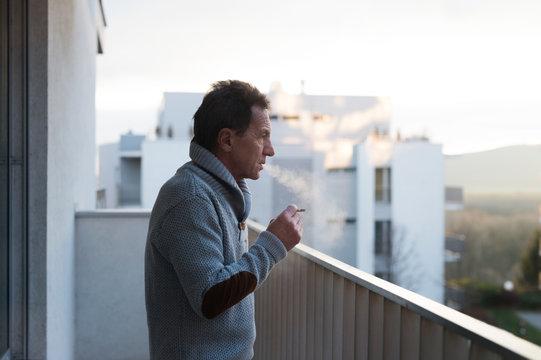Serious senior man standing on balcony, smoking a cigarette