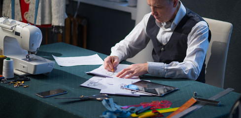 Tailor in the studio suit draws on paper.