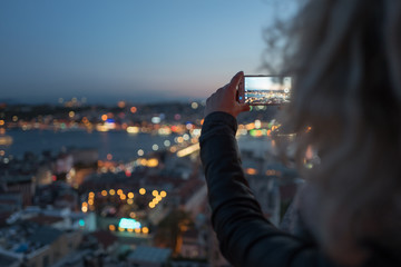 Blonde woman is making photo on her phone of Istanbul from Galata Tower viewing platform