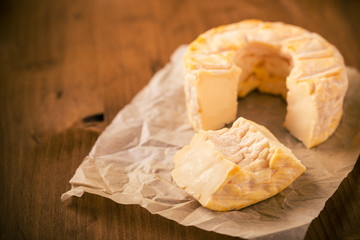 Portion cut from whole golden camembert cheese on wooden table