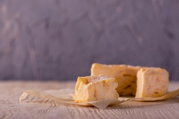 Portion of golden camembert on white wooden board