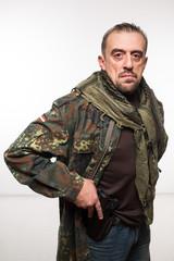 Male terrorist. military jacket. gun in his hand.