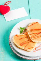 Breakfast on Valentine's Day: Pancake in the form of hearts with red sauce, a cup of coffee, a note or love confession and a red plush heart toy. On a light blue wooden table, copy space