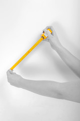 Tape measure in hands on white