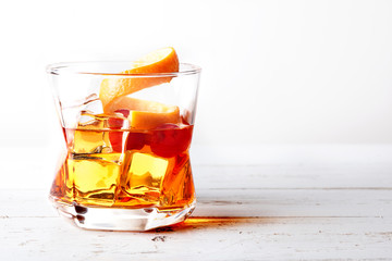 Glass of old fashioned whiskey with ice, orange and cherries over a white wood table