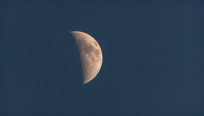 Moonshine in the dusky evening sky.  Half moon shines in evening deep blue sky.