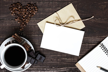 coffee cup and heart shaped beans with greeting card and notebook