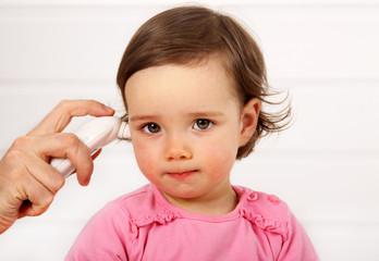 Einem Kleinkind wird im Ohr Fieber gemessen.