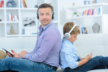 Father and son wearing headphones, back to back