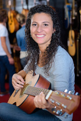 Portrait of young woman playing guitar