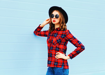 Fashion young woman posing wearing a black hat, red checkered sh