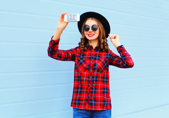 pretty young smiling woman taking picture self portrait on smart