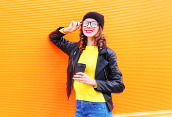 Fashion pretty smiling woman with coffee cup wearing a black hat