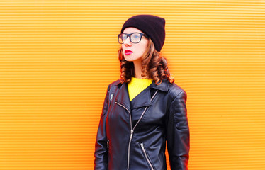Fashion pretty woman in black hat and rock jacket over colorful