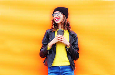 Fashion pretty young smiling woman with coffee cup wearing a bla