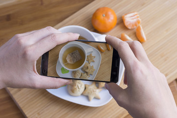 Woman taking photo of tea breakfast with mobile phone
