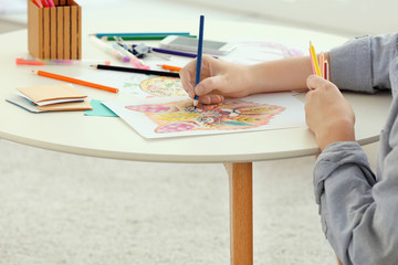 Young woman sitting at table with coloring pictures for adults