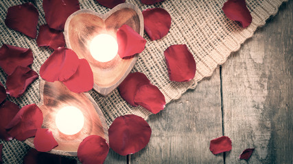 Two enlightened candles in heart-shaped candleholders with rose