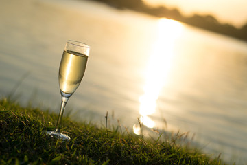 A glass of Champagne on grass at river side In the evening background