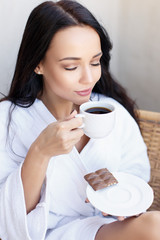 Young girl in a white bathrobe with cup of coffee