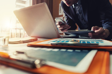 businessman working with digital tablet computer and smart phone with financial business strategy layer effect on desk in morning light.vintage effect