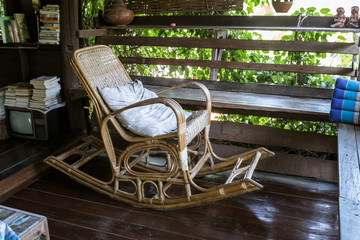 Wicker rocking chair on a wooden house in the old atmosphere in the morning.