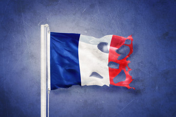 Torn flag of France flying against grunge background