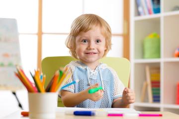 Cute little preschooler child drawing with felt pen at home